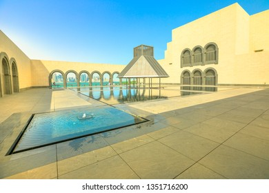 Doha, Qatar - February 16, 2019: Courtyard of Museum of Islamic Art with fountains and arched windows opening view on Doha West Bay and Persian Gulf reflecting in a pool.