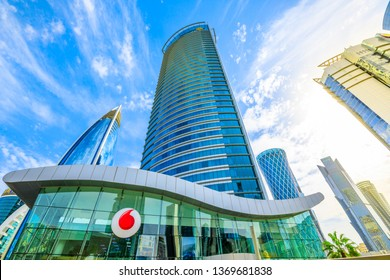 Doha, Qatar - February 17, 2019: bottom view of Vodafone Headquarters and logo brand in Qatar West Bay area. Glassed skyscraper in Doha Downtown, Middle East. Urban scene.