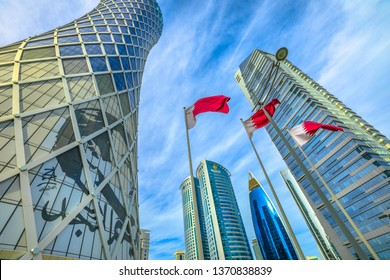 Doha, Qatar - February 17, 2019: Tornado Tower with image of Emir Tamim bin Hamad al-Thani and Flag of Qatar. High rises in West Bay. Skyscrapers of Financial District in Middle East, Persian Gulf.