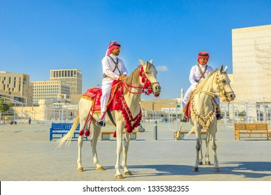 Doha, Qatar - February 20, 2019: two heritage Police Officers in traditional 1940s Qatari uniform riding white Arabian Horses at square of Souq Waqif. Popular tourist attraction in Doha city center.