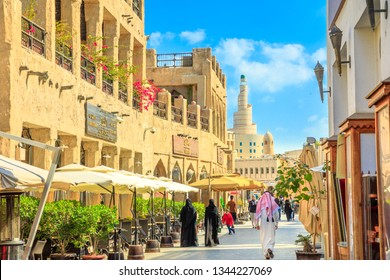 Doha, Qatar - February 20, 2019: women and men in traditional Arab clothing walk along main street inside Souq Waqif old market with cafes and restaurants.Fanar Islamic Cultural Center in the distance