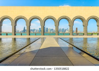 Doha, Qatar - February 20, 2019: Doha West Bay skyline through arches in courtyard of Museum of Islamic Art along water features in a sunny day. Popular tourist seafront. Middle East in Persian Gulf.