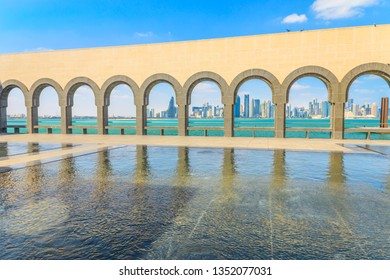 Doha, Qatar - February 20, 2019: modern skyscrapers of Doha West Bay skyline through a series of arches in courtyard of Museum of Islamic Art. Popular tourist seafront. Middle East in Persian Gulf.