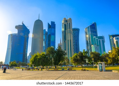 Doha, Qatar - February 20, 2019: Woqod Tower, Alfardan Towers and Doha Tower, iconic glassed high rises in West Bay from Sheraton Park along corniche promenade at sunset. Middle East in Persian Gulf.