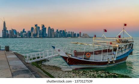 Doha, Qatar - February 2019: Doha Qatar skyline with traditional Qatari Dhow boats in the harbor