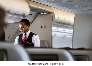 Doha, Qatar - February 20th, 2019: A male cabin crew flight attendant speaking with a passenger onboard on Airbus A350 of Qatar Airways.