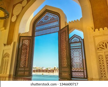 Doha, Qatar - February 21, 2019: Doha West Bay skyline view from State Grand Mosque in Doha, Qatar, Middle East, Arabian Peninsula. Door of entrance at Mosque in Arabian style. Sunny day with blue sky