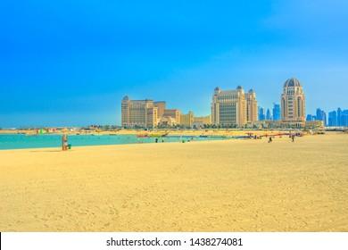 Doha, Qatar - February 22, 2019: gold sand of Katara Beach with the St. Regis Doha in luxury hotel on background. West Bay, Doha Bay area near Katara cultural village. Blue sky with copy space.