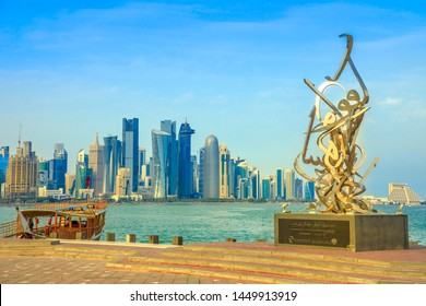 Doha, Qatar - February 23, 2019: Calligraphy sculpture on the corniche seaside promenade, wooden dhow and Doha West Bay skyline with Doha Tower, Salam Tower, World Trade Center on background.