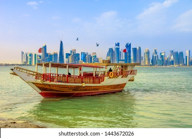 Doha, Qatar - February 23, 2019:traditional dhow and seafront of Doha West Bay skyline on background with Qatar International Exhibition Center, Doha Tower, Salam Tower, World Trade Center, Bank Tower