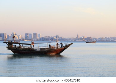 DOHA, QATAR - JANUARY 31, 2016: Dhows running pleasure trips around Doha Bay return to shore as the sun sets on the Qatari capital city. Visible faces  in the nearest dhow.