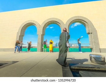 Doha, Qatar - January 5, 2019: Courtyard of Museum of Islamic Art with arched windows opening view on Doha West Bay skyline and Persian Gulf. Arabs and tourists visit the popular museum. Sunny day.