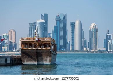 DOHA, QATAR - JANUARY 8, 2019: Traditional Arabic Dhow boats with Qatar flags in Doha, Qatar National day preparation. Doha, Qatar, Middle East.