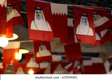 DOHA, QATAR - JULY 6, 2017: National flags  with images of Qatari Emir Sheikh Tamim strung across the ceiling the  in Souq Waqif market during the crisis between Qatar and neighbouring Arab states