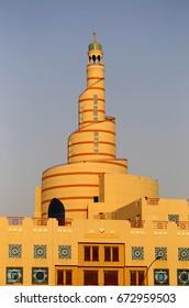 DOHA, QATAR - JULY 6, 2017: The landmark spiral minaret of Qatar's Islamic Centre, catches the late afternoon sun.