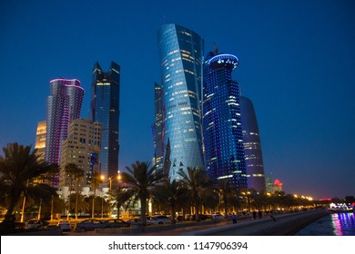 Doha/ Qatar - March 23 2017:  Doha skyline in front of Corniche Street in the evening with trees in front of them, a modern and very rich Arab city which is growing rapidly