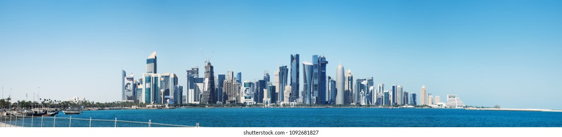 Doha, Qatar - March 3, 2018: The morning panoramic view of the skyscrapers of Doha from the Persian Gulf. Futuristic skyline in the financial district of Qatar and embankment with moored ships