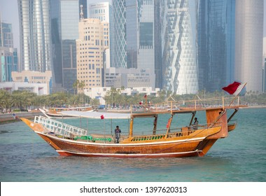 Doha, Qatar- May 14 2019. Dhow near West bay sky scrapers is an iconic water taxi. Traditional boat made from wood.Located at Doha corniche. A fishing or pearl boat in the past.A heritage for Qatar.