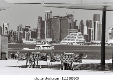 DOHA, QATAR - May 2018: Restaurant chairs and awning, overlooking Doha, Qatar, towers with a ferry to Banana Island passing by. Shot on black and white film with grain