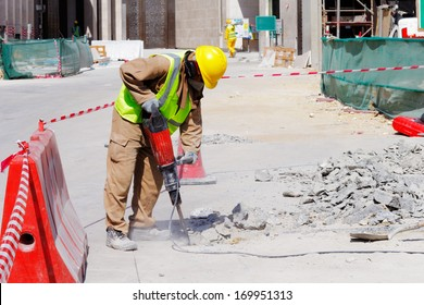 DOHA, QATAR - NOV 13: A laborer is well protected in safety gear as he uses a jackhammer to break up a reinforced concrete pavement on Nov 13, 2013 in Doha, Qatar.