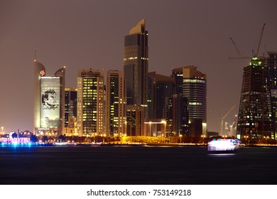 DOHA, QATAR - NOVEMBER 11, 2017: City skyline at night with the Commercial Bank's tower and poster of Emir Tamim bin Hamad on the left. A brightly lit dhow has motion blur bottom right.