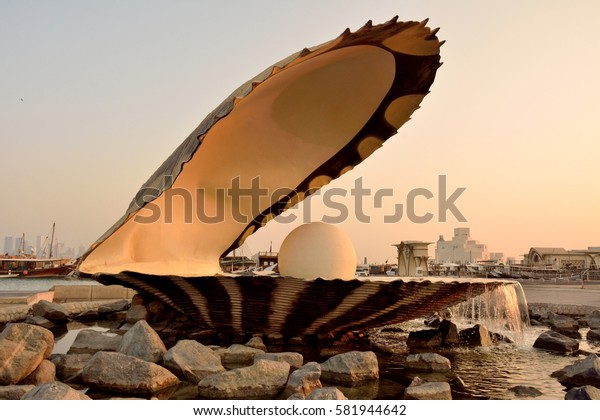DOHA, QATAR - NOVEMBER 2, 2016. Pearl monument in Doha, with people, cars, boats and buildings in the background, at dawn.