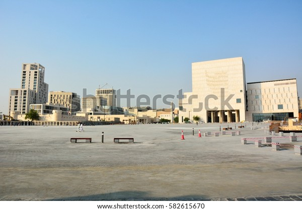 DOHA, QATAR - NOVEMBER 2, 2016. View of public square in Doha with Doha Fort, modern residential and commercial buildings and people.