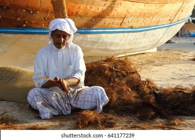 Doha  / Qatar – November, 2014:  local old man making ropes in a traditional way near the beach of Doha During a traditional festival / Qatari Traditional festival
