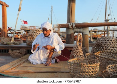 Doha - Qatar / November 2017: Kuwaiti craftsman making traditional fishing baskets During the Dhow festival at Katara beach.