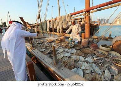 Doha - Qatar / November 2017: Omani fisherman selling dried and smoked fish to a Qatari buyer During the Dhow festival at Katara beach.