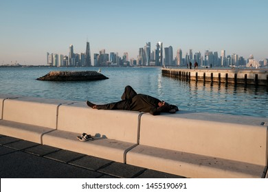 Doha, Qatar - November 23 2018: A worker taking a nap at the Corniche on a late afternoon, with the iconic Doha skyline in the background.