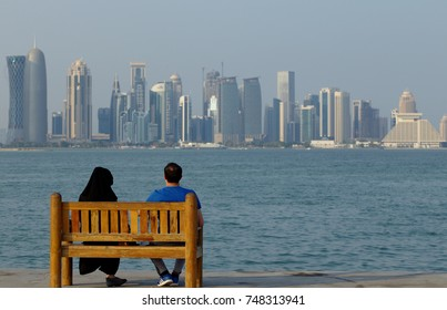DOHA, QATAR - NOVEMBER 4, 2017:  A Muslim couple enjoy the view from the Corniche in Doha Bay.