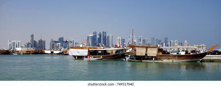 DOHA, QATAR - NOVEMBER 6, 2017: View of the dhows moored in Doha Bay from the Corniche, with the distant business towers forming the skyline
