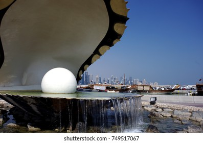 DOHA, QATAR - NOVEMBER 6, 2017: View of Doha Bay from the Corniche, with the oyster nd pearl fountain and the distant business towers beyond the dhow harbour