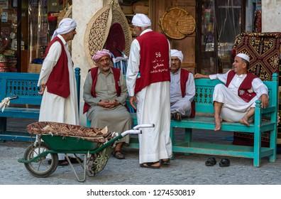 Doha, Qatar - November 9, 2016. Alhmalah porters in numbered maroon waistcoats enjoying free time in Doha.