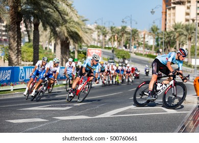 Doha, Qatar - October 16, 2016: Cyclists round a corner at the Pearl during the elite men's road race at the UCI Road World Championships.