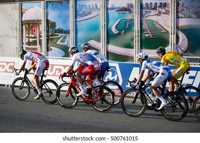 Doha, Qatar - October 16, 2016: Cyclists pass by a billboard with an aerial view of the Pearl toward the end of the elite men's road race at the UCI Road World Championships.