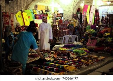 DOHA, QATAR - OCTOBER 23, 2017: Shoppers buying textiles in Souq Waqif market in Qatar, Arabia, at night