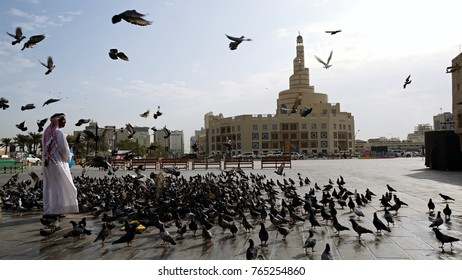DOHA, QATAR - OCTOBER 23, 2017:   A Qatari man feeding a group of pigeons in Souq Waqif with a background of Al Fanar Islamic centre building.