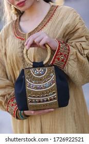 Doha, Qatar - September 10, 2019: Young fashion woman hold handbag clutch with traditional dress matching