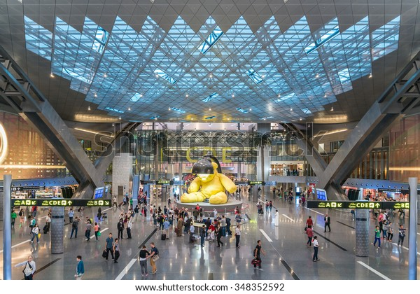 DOHA, QATAR - SEPTEMBER 16, 2014: Interior of Hamad International Airport Terminal full of Tourist People Passenger, Big Yellow Bear Sculpture, Executive Airline VIP Lounge, Middle East