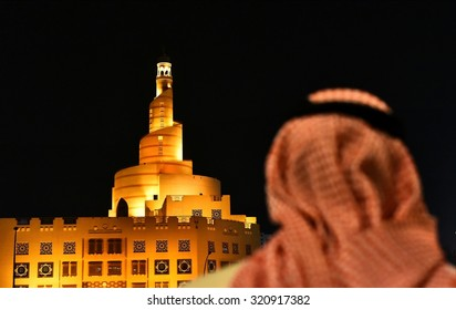 DOHA, QATAR - SEPTEMBER 18, 2015: Arab man standing in front of the spiral mosque, one of Doha's most famous landmarks. It is located in Qatar Islamic Culture Center.