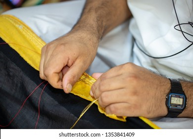DOHA, QATAR - SEPTEMBER 22, 2014: Hands with black watch sewing to create a bisht.