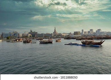 Doha , Qatar-September 6 2020: Doha skyline from the cor-niche promenade sunset shot showing dhow with Qatar flag in the Arabic gulf  in foreground and clouds in the sky in background