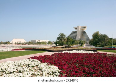 The Doha Sheraton Hotel, Qatar, from the roundabout at the entrance, across a sea of petunias (Feb 2007). The building on the left is the Conference Centre.