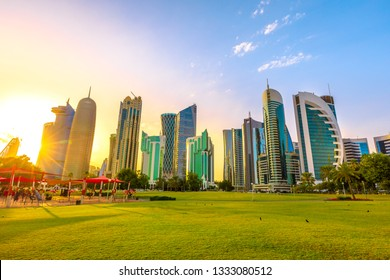 Doha West Bay high rises at sunset from green lawn of a park along corchiche promenade. Modern skyscrapers of Doha skyline in Qatar, Middle East, Arabian Peninsula in Persian Gulf.