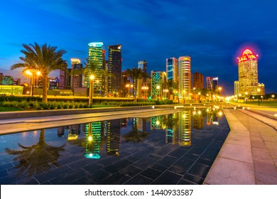 Doha West Bay high rises at evening reflections of downtown park. Lighting skyscrapers of Doha skyline in Qatar, Middle East, Arabian Peninsula in Persian Gulf. Night cityscape scene.
