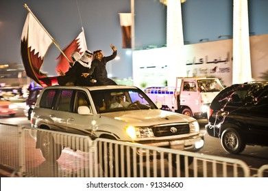 DOHA-DEC 18: Qataris with flags sit or stand on a vehicle during a parade to celebrate their National Day, on December 18, 2011 in Doha, Qatar.  This has been an annual event since 2009.