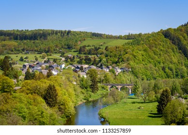 Dohan in Ardennes. Small village in the countryside along river Semois. Bridge on Semois river. Agriculture landscape with houses of Dohan on hill in the background. Ardennes region, Wallonia, Belgium
