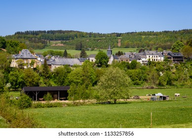 Dohan. Small village in the countryside along river Semois. Agriculture landscape with houses of Dohan in the background. Ardennes region, Wallonia, Belgium.
